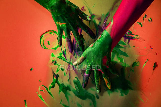 Crop unrecognizable female artist staining colorful wall with paint on gradient colorful background in studio — Stock Photo