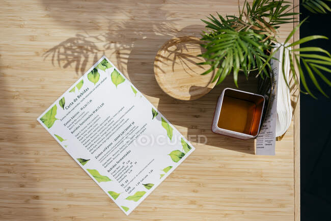 Top view of menu laminated paper composed on wooden table near flowerpot and various wooden and metallic items — Stock Photo