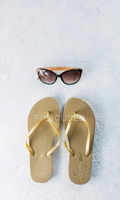 Top view of pair of flip flops placed near trendy sunglasses for summer vacation on plaster surface — Stock Photo