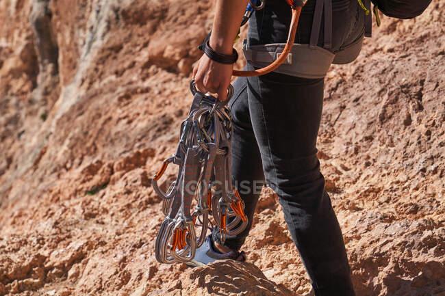 Vista laterale dell'arrampicatore anonimo in abiti casual che cammina su un sentiero roccioso vicino alla montagna e porta diverse rinvii in mano — Foto stock