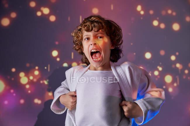 Menino com cabelo encaracolado gritando alto com a boca aberta olhando amplamente para a câmera enquanto estava de pé com as mãos no quimono branco aberto no quarto de néon brilhante — Fotografia de Stock