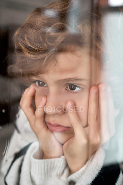 Скучный мальчик смотрит в мокрое окно — стоковое фото