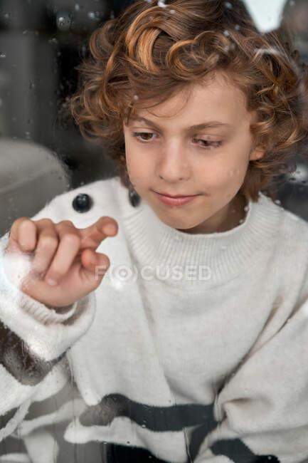 Мальчик рисует на мокром стекле — стоковое фото