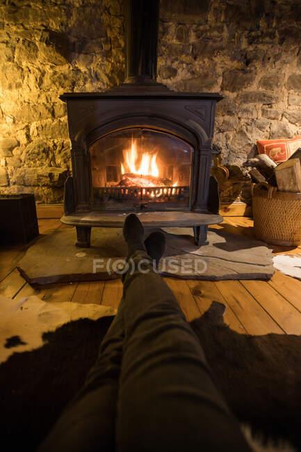Pessoa anônima em roupas casuais sentado com pernas esticadas perto de lareira em chamas na acolhedora sala de estar da antiga casa de pedra — Fotografia de Stock