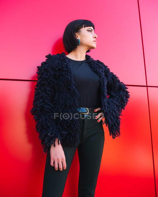 Basso angolo di femmina indossa abbigliamento nero alla moda in piedi con mano sulla vita contro il muro rosso in città e guardando altrove — Foto stock