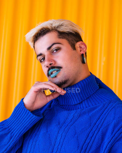Androgynous male with blue lips and in stylish wear standing on background of yellow wall in city while looking at camera and touching face — Stock Photo