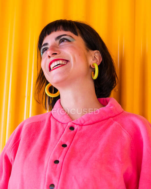 Low angle of cheerful female in pink clothes and with red lips standing against yellow wall in urban area and looking up — Stock Photo