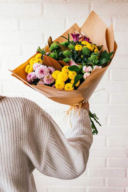 Cultiver une personne méconnaissable debout avec un bouquet de fleurs fraîches et colorées sur fond de mur de briques blanches — Photo de stock