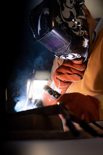 Unrecognizable male employee in protective gloves and helmet using welding machine while working in dark workshop — Stock Photo