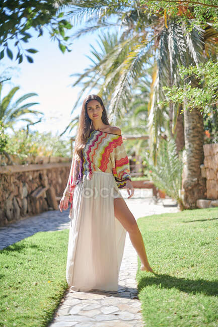 Full body of barefoot young beautiful ethnic female model wearing stylish summer clothes looking at camera while standing on stone pathway against tropical garden — Stock Photo