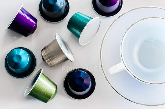 Top view of collection of coffee pods placed near empty ceramic mug and saucer on white background — Stock Photo