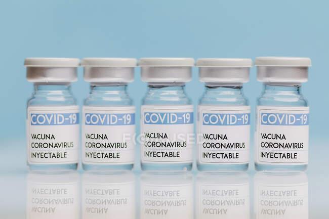 Flacons en verre avec vaccin de COVID 19 placés sur la table en rangée sur fond bleu — Photo de stock