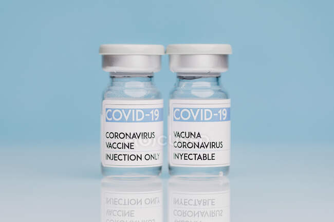 Frascos de vidro com vacina COVID 19 colocados sobre a mesa sobre fundo azul — Fotografia de Stock