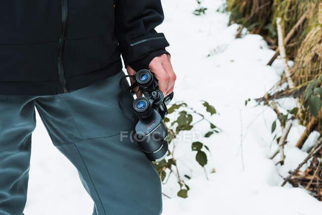 Escursionista maschio irriconoscibile ritagliato in abiti caldi in piedi in boschi invernali innevati con binocolo — Foto stock