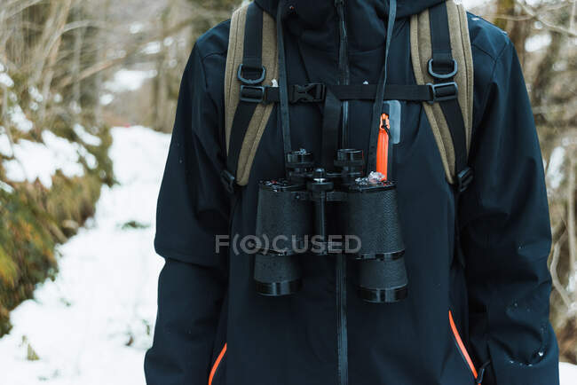 Cropped unrecognizable male hiker in warm clothes standing in snowy winter woods with binoculars — Stock Photo