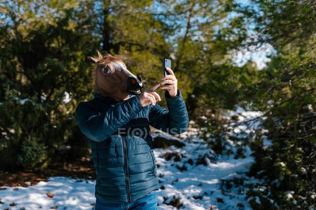Hombre irreconocible usando máscara de caballo raro tener videollamada en el teléfono inteligente mientras está de pie en los bosques nevados de invierno y la mano ondulante - foto de stock