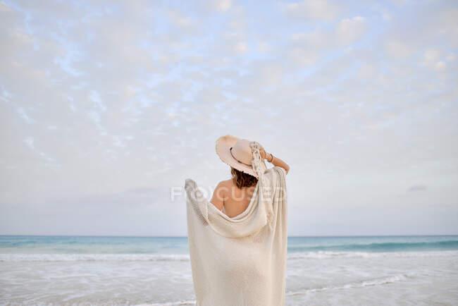 Жінка - мандрівник у капелюсі стоїть вздовж берега і озирається назад. — стокове фото