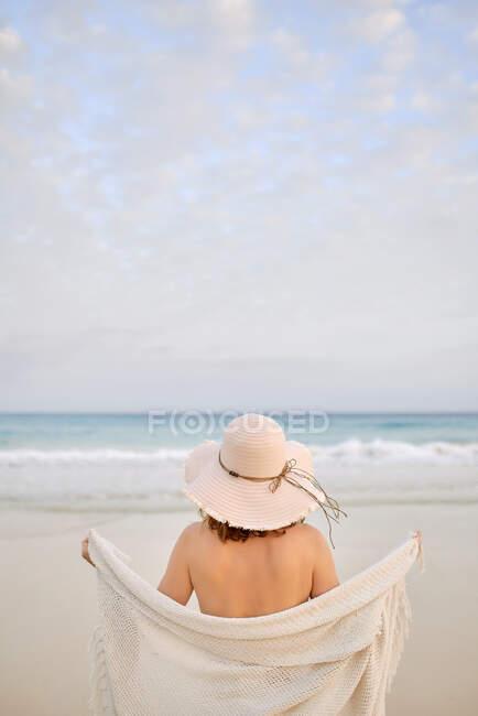 Back view viaggiatore femminile in cappello in piedi lungo la riva del mare e guardando altrove — Foto stock