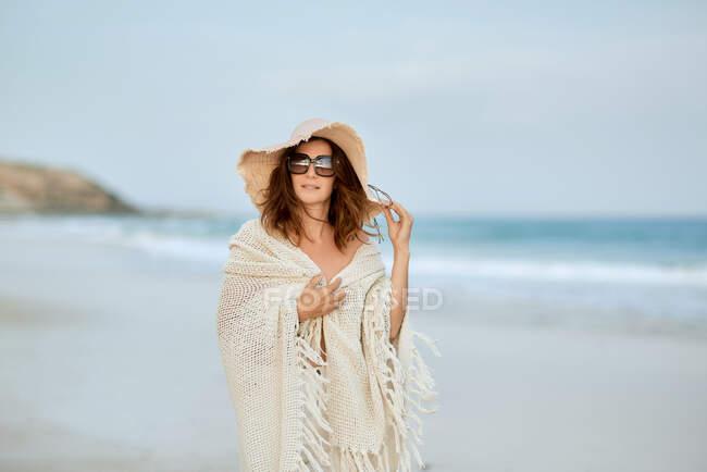 Reisenden mit Sonnenbrille und Hut entlang der Küste und Blick in die Kamera — Stockfoto