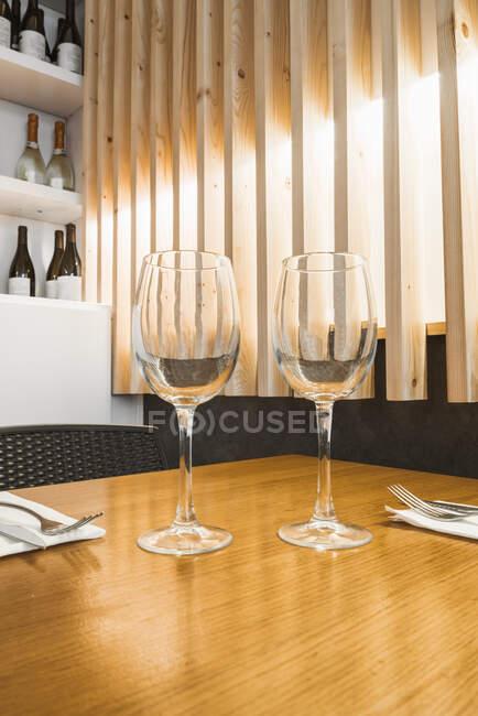 Taças vazias frágeis em pé sobre mesa de madeira — Fotografia de Stock