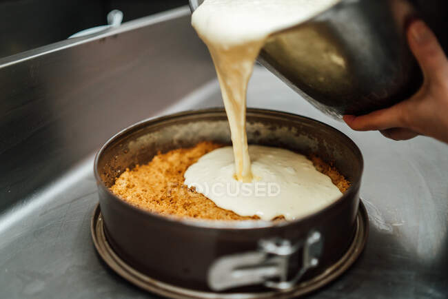 Cropped unrecognizable cook pouring cream on cake tin while preparing delicious cheesecake dessert in cafe — Stock Photo