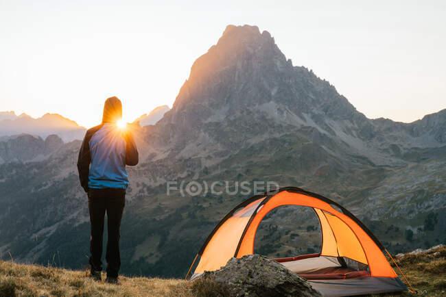Vue arrière d'un randonneur méconnaissable debout sur une colline près d'une tente admirant la vue sur la chaîne de montagnes pittoresque des Pyrénées le matin — Photo de stock