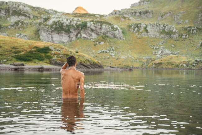 Обратный вид на неузнаваемого путешественника с обнаженным торси, стоящим в Лакс-д-Айос в высокогорной местности в Пиренеях — стоковое фото