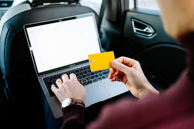 High angle of crop anonymous male entrepreneur sitting on backseat of luxury automobile with laptop and making online purchase while using plastic card — Stock Photo