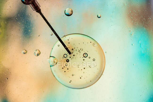 Acercamiento de la aguja de la jeringa llena de vacuna del virus inyectado en la célula sobre fondo borroso - foto de stock