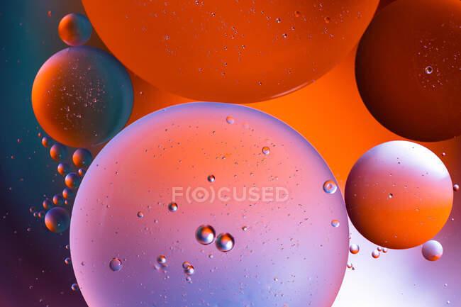Primer plano de fondo abstracto con células redondas de vacuna de diferentes tamaños iluminadas por luz colorida - foto de stock