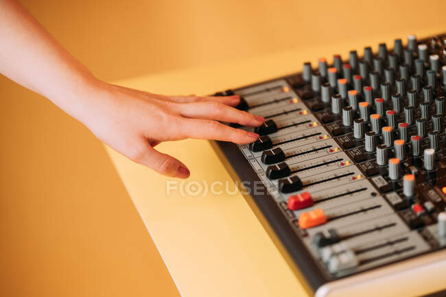 Crop hand of woman using equalizer in music studio on blurred background — Stock Photo