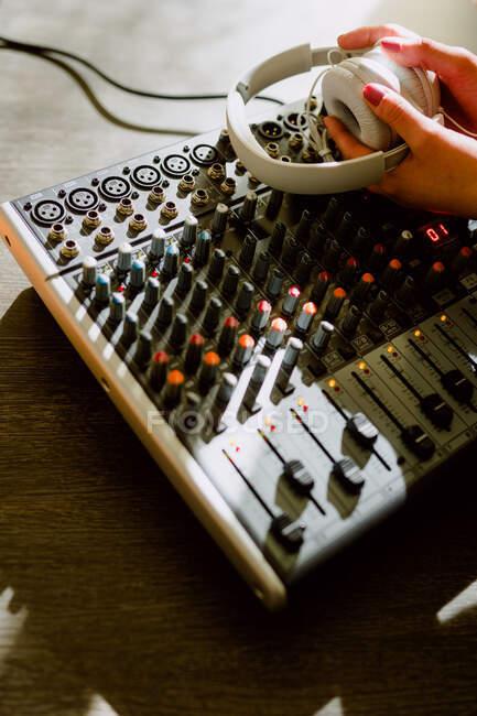 Mão de corte de mulher usando equalizador no estúdio de música em fundo embaçado — Fotografia de Stock