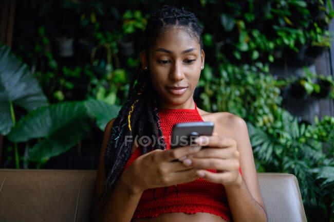 Retrato de mujer latina afro joven atractiva con rastas en un top rojo del ganchillo usando smartphone en mesa de restaurante, Colombia - foto de stock