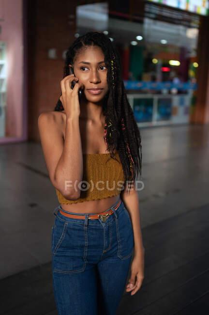 Portrait d'une jolie jeune femme afro latine parlant sur un smartphone dans un centre commercial, en Colombie — Photo de stock
