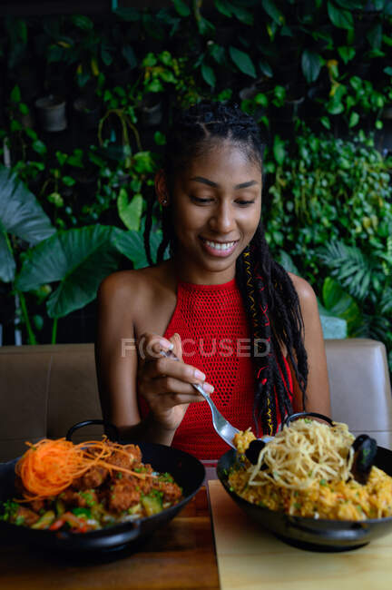 Portrait of attractive young afro latin woman with dreadlocks in a crochet red top eating in Asian restaurant, Colombia — Stock Photo
