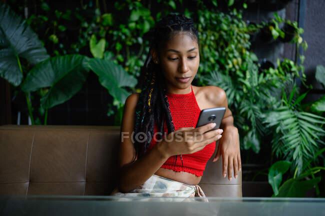 Portrait de attrayant jeune femme afro latine avec dreadlocks dans un crochet haut rouge en utilisant smartphone dans la table du restaurant, Colombie — Photo de stock