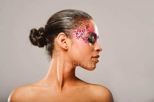 Portrait of brunette woman with ponytail and makeup eyes looking down — Stock Photo