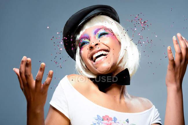 Chica rubia con pelo corto y maquillaje colorido divirtiéndose con confeti - foto de stock