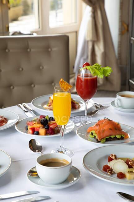 Varios platos coloridos y jugos servidos en la mesa redonda durante el desayuno en el elegante restaurante del hotel en la mañana soleada - foto de stock