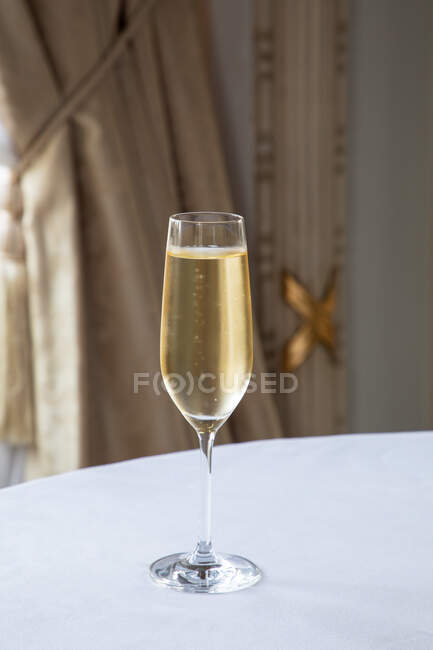 Crystal glass of sparkling wine served on white round table in elegant restaurant in daylight — Stock Photo