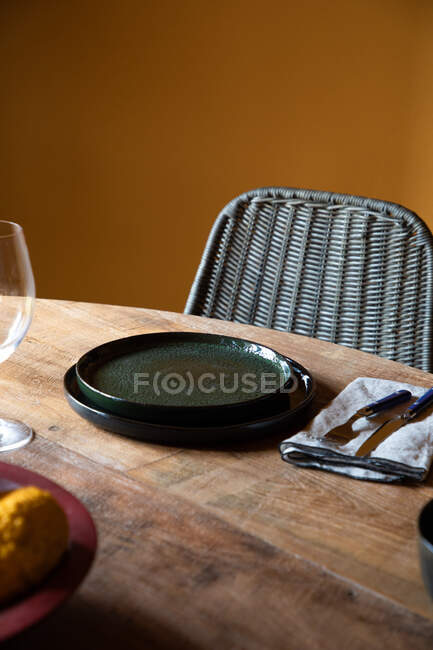 From above of wooden table with ceramic plates and cutlery on napkin near wineglass in restaurant — Stock Photo