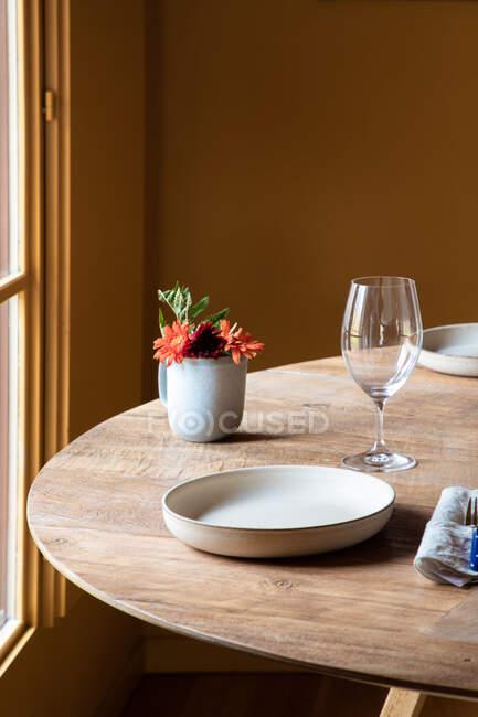 Serviertisch mit Keramiktellern mit Besteck auf Serviette neben Weingläsern und Blumen mit Früchten — Stockfoto