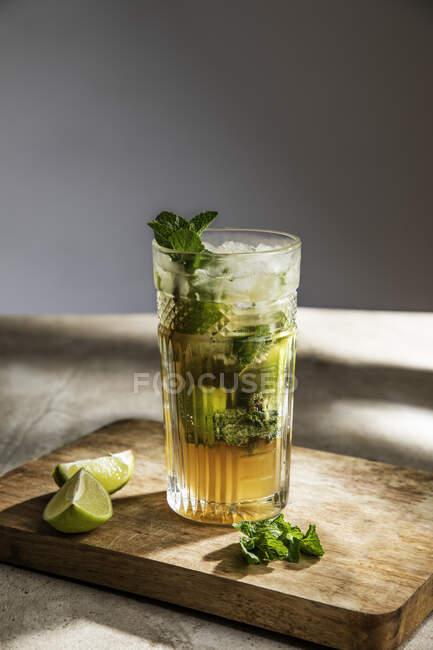 Mojito rinfrescante freddo alcolico con foglie di menta ghiacciata e lime tagliato su tavola di legno — Foto stock