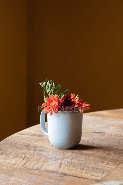 Керамічна чашка з свіжими квітучими квітами, розміщеними на дерев