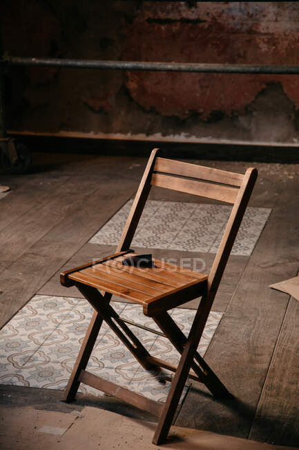High angle of chair placed on dusty parquet and tile floor in messy room during repair works — Stock Photo