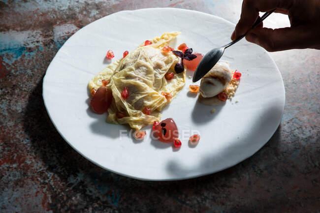 Von oben von der Ernte anonyme Person essen leckere Omelett mit Granatapfelkernen dekoriert — Stockfoto