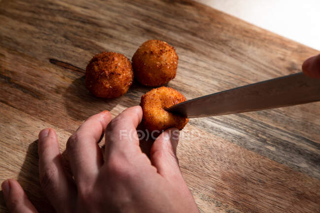 From above of crop anonymous cook cutting crispy deep fried cheese ball on wooden cutting board — Stock Photo