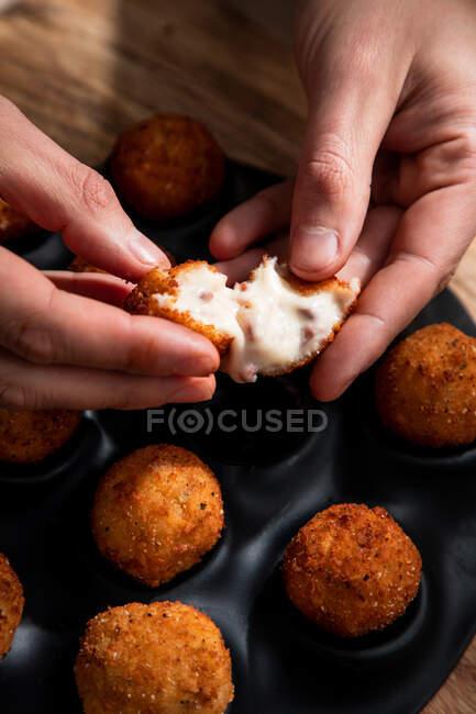 Von oben demonstriert anonymer Koch die Füllung von Käsekugeln in knuspriger Kruste in der Küche — Stockfoto