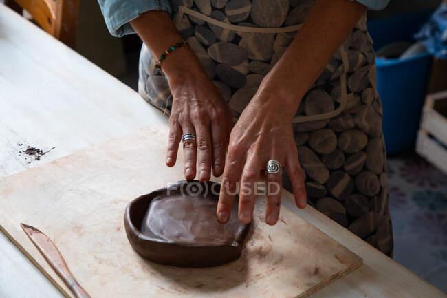 Сверху на урожай анонимный мужчина ремесленник прокатки глины кусок во время создания плиты в мастерской — стоковое фото