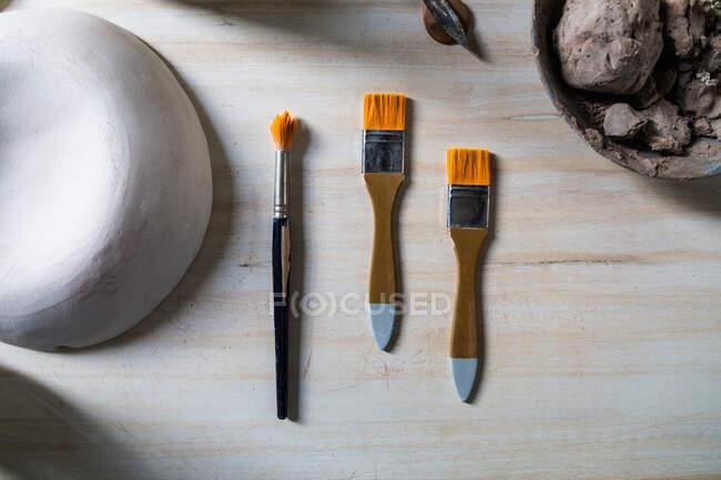 Vista dall'alto set di ceramiche e pennelli posati su tavolo in legno con ciotola di argilla e vaso in ceramica in officina — Foto stock